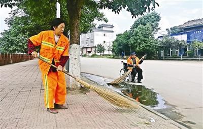雷通兴坐着轮椅,陪着环卫工妻子薛桂兰清扫路面