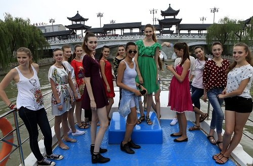 资料图片:2014年8月15日,参加2014新丝路国际旅游形象大使大赛的中外模特在扬州乘船游览大运河。新华社记者 李明放 摄