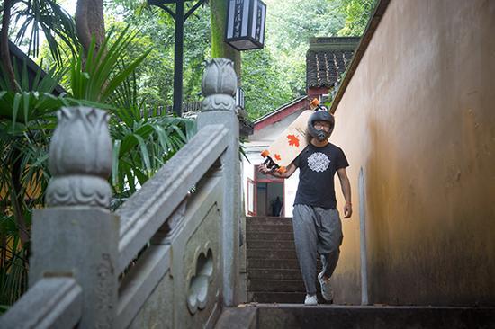 赵莲贵拿着喜爱的滑板走下山。 本文图片来源: 受访者供图、东方IC