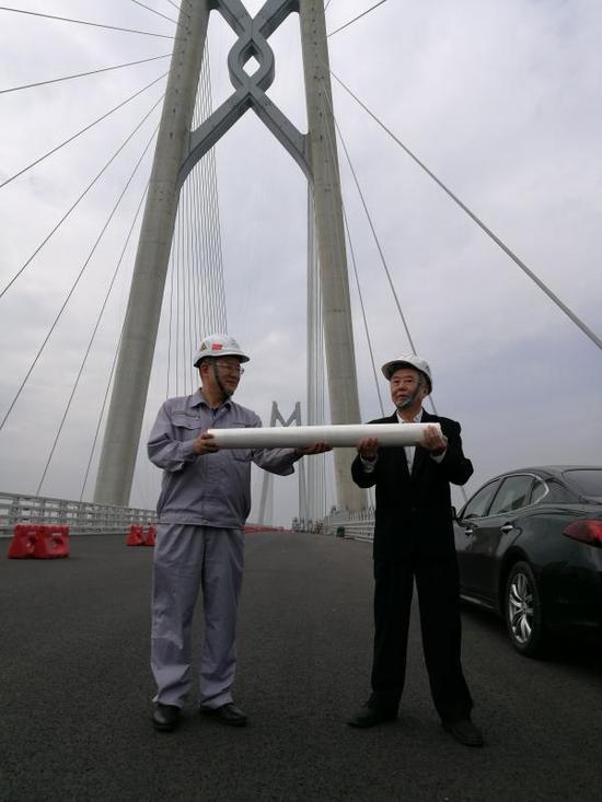 """港珠澳大桥管理局党委副书记、行政总监韦东庆在青州航道桥""""中国结""""下代表建设者从林老手中接过画卷。"""