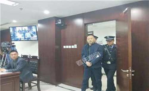 图为石某被带进法庭。摄/记者 李夏
