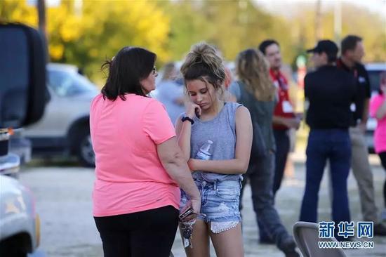 11月5日,在美國德克薩斯州南部薩瑟蘭斯普林斯發生槍擊事件的教堂外,一名母親安慰自己的女兒。新華社發(顔博攝)
