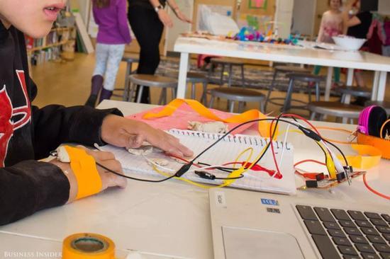 ▲一个8岁的小男孩正在设计如何用泥块代替方向键操纵游戏。图据《商业内幕》