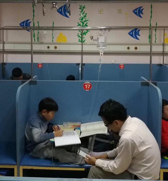 11月6日傍晚,普陀区人民医院内,一名学生边输液边写作业。新民晚报记者 孙中钦 图