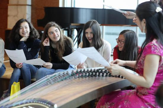 """2017年5月5日,在中国驻美国纽约总领馆举行的""""感知中国""""活动中,一名老师为美国学生展示古筝弹奏。(新华社记者王迎摄)"""