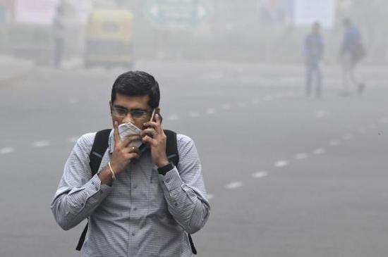 11月8日,在印度新德里,一名男子在雾霾天气里出行。