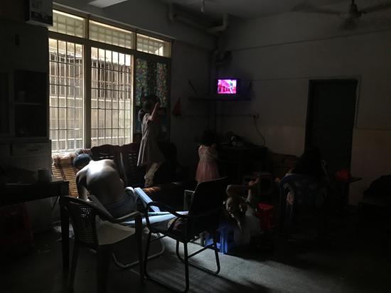 大大小小的女孩们围在一起,王忠馗弓着背坐在一旁。这间屋子是邻居借给一家十口暂住的。