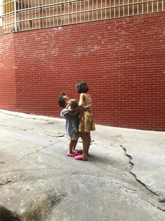 最小的妹妹被姐姐们轮流抱着。