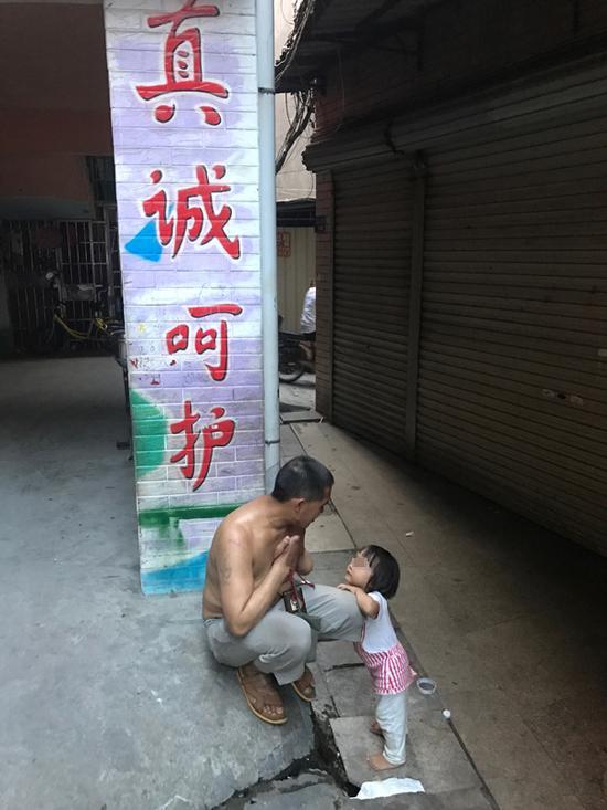 """王忠馗和七女儿在家门口,身后是邻近幼儿园的彩绘,写着""""真诚呵护""""。"""