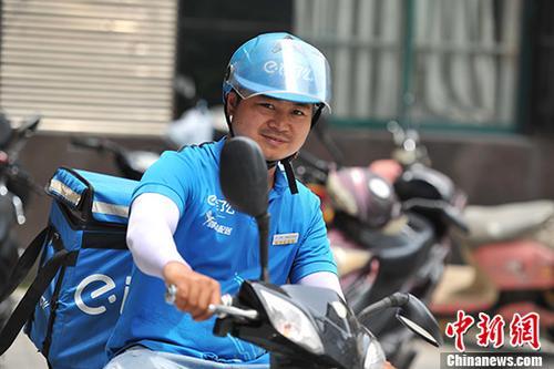 送餐员在送外卖路上(资料图)。 中新社记者 刘占昆 摄