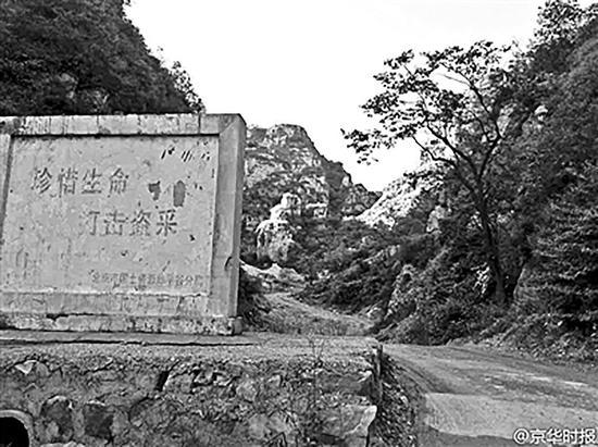 """在前往矿井的路上,立着""""珍惜生命 打击盗采""""的警示碑"""