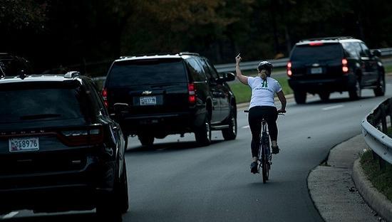 今年10月底,美国总统的车队在华盛顿郊区经过一名骑着自行车的女子时,被这名女子以比中指做为回应。来源:视觉中国