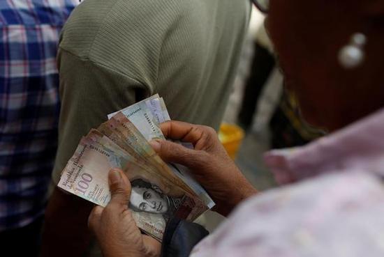 当地时间2017年11月13日,委内瑞拉首都加拉加斯,一个妇女在菜市场清点手头的纸币。标普将委内瑞拉的长期外币主权信用评级从CC级下调至SD级。  视觉中国 图