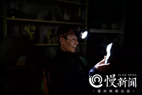 罗长国的奇石展览区光线很暗,戴着头灯欣赏自己的收藏,他的脸上流露出欢喜