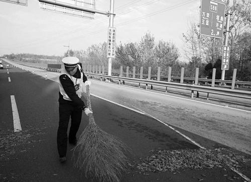 民警在高速路上清扫撒了一地的辣椒