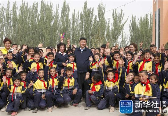 2014年4月28日,习近平在新疆疏附县托克扎克镇中心小学同师生们合影。新华社记者 谢环驰 摄