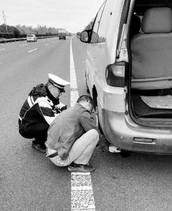 今年10月18日,史伟年资助司机为故障车辆替换轮胎。