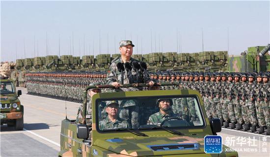 2017年7月30日,解放军建军90周年前夕,在内蒙古朱日和基地,习近平身穿绿色迷彩服,登上越野车,检阅野战部队。新华社记者 李刚 摄