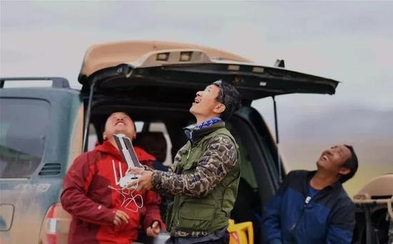 ▲6月23日,中科院动物研究所副研究员李欣海(中)在使用无人机查看考察区域内的动物种群分布情况