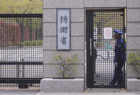 资料图片:在日本东京的防卫省总部,一名工作人员在大门旁守卫。新华社发
