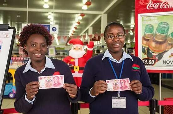 ▲资料图片:津巴布韦一家超市的两名售货员手持人民币拍照。目前,人民币在津巴布韦是合法支付货币。