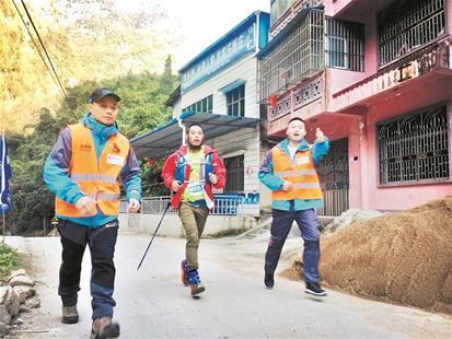 图为朱天波(中)在志愿者引导下奔跑