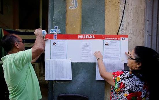 当地时间2017年11月26日,古巴哈瓦那,古巴举行市政选举,工作人员在张贴候选人信息。 视觉中国 图