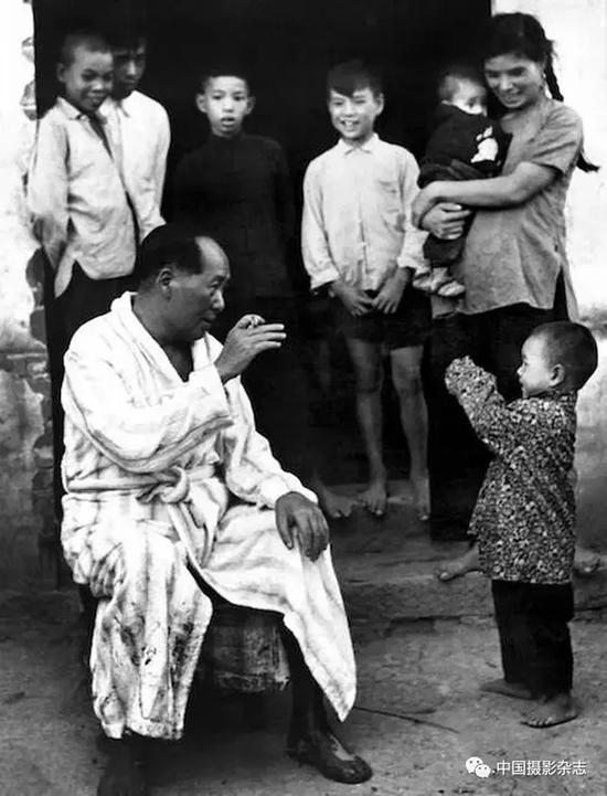 毛泽东畅游湘江后在农家门口与小孩逗趣,1958年 侯波 摄