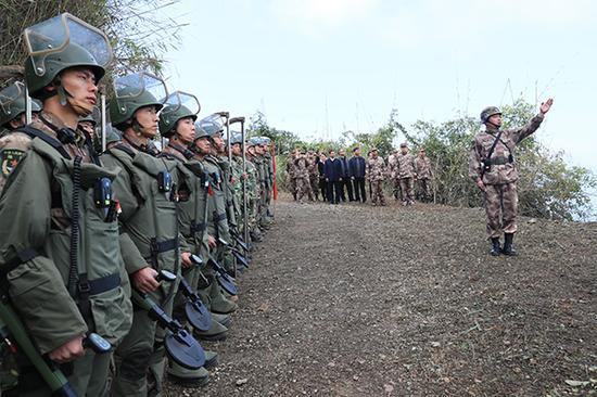 扫雷战士们穿戴防护装置和手拿扫雷仪器,准备开赴雷场。 本文图均为郝�Q 张峻森 图