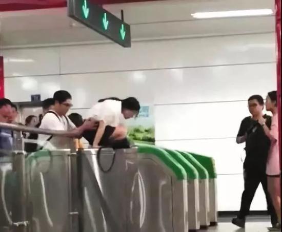 """▲一女子在男同伴的""""扶助""""下,爬过地铁检票闸机口。视频截图"""