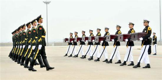 3月28日,在韩国仁川国际机场,韩方(右)向中方礼兵移交中国人民志愿军烈士遗骸。(新华社)