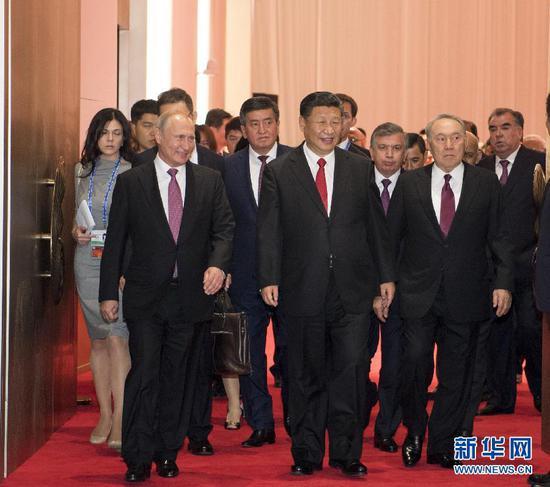 6月9日,国家主席习近平在青岛国际会议中心举行宴会,欢迎出席上海合作组织青岛峰会的外方领导人。这是习近平同贵宾们共同步入宴会厅。新华社记者李学仁摄