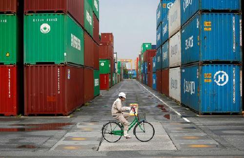 一名工人骑车穿过东京一处港口的集装箱停放区。(路透社)