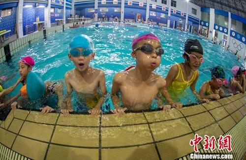 7月26日,学童们在江西新余市体育中心游泳馆学习游泳。入伏以来,江西高温范围明显扩大,多地最高气温超过38℃,未来一周,该省仍持续晴热高温天气。中新社发 赵春亮 摄