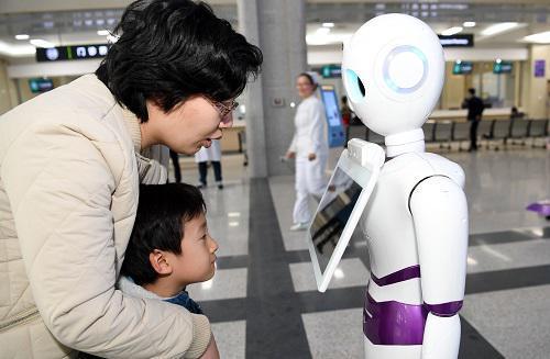 市民在位于合肥的安徽省立医院南区感受机器人导诊服务(2017年12月23日摄)。 新华社记者 刘军喜 摄