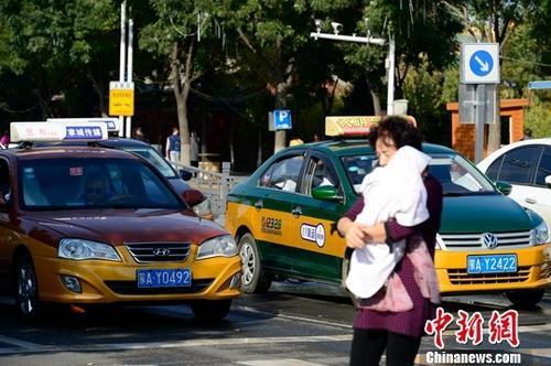 资料图:等红灯的出租车。中新社记者 刘文华 摄