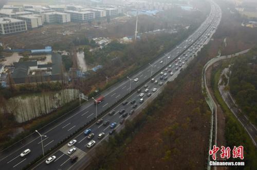 资料图:2月21日,大批车辆由北向南缓慢行驶在南京二桥高速公路上,绵延数公里。 中新社记者 泱波 摄