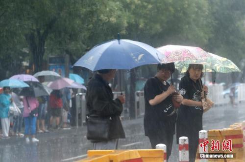 资料图:北京市民众冒雨出行。中新社记者 盛佳鹏 摄