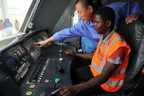"""资料图片:2016年5月13日,尼日利亚阿卡铁路即将试运行,来自中国的技术人员正在列车驾驶室里向当地工作人员""""传授技艺""""。"""