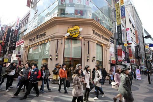 资料图片:2011年3月2日,人群经过韩国首尔明洞购物区的一家服装店门口。新华社记者 何璐璐 摄