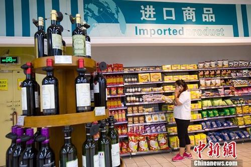 资料图:山西太原,民众在超市挑选进口商品。中新社记者 张云 摄