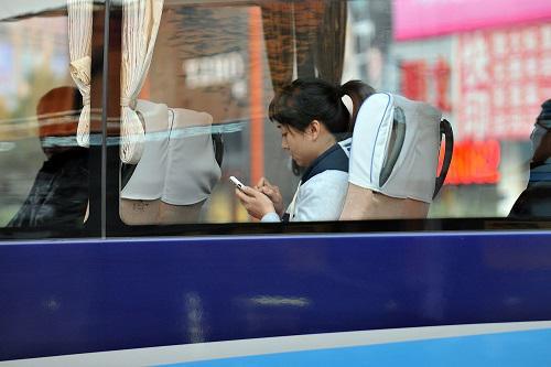 一位女士在公交车上使用手机。新华社记者 詹彦 摄