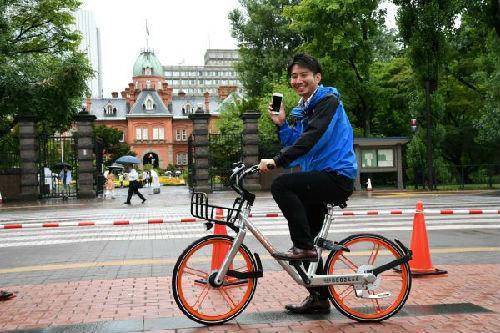 2017年8月22日,在日本北海道札幌市,一名当地电视台记者试乘摩拜单车。(新华社)