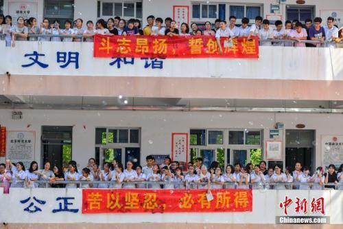 """资料图:5月31日,海南华侨中学举行一年一度的""""高考文明喊楼""""活动。同学们齐喊""""高考加油!""""""""老师我爱您!""""等口号。整个过程持续半小时,场面壮观。中新社记者 骆云飞 摄"""