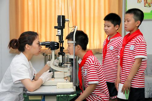 6月6日,在石家庄市西里小学,医护人员为小学生进行视力检查。新华社发