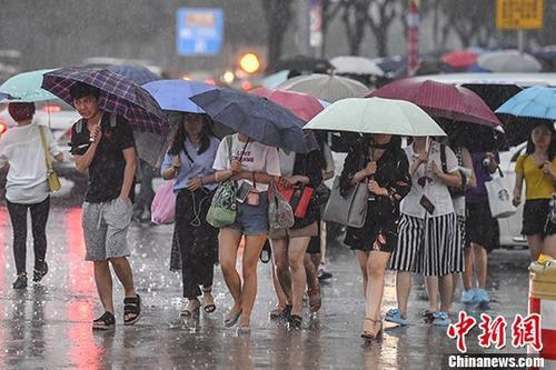 廣州民衆在暴雨中出行。 中新社記者 陳驥旻 攝