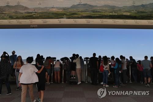 资料图片:从都罗山�t望台遥望非军事区和开城工业园的各国游客们(韩联社)