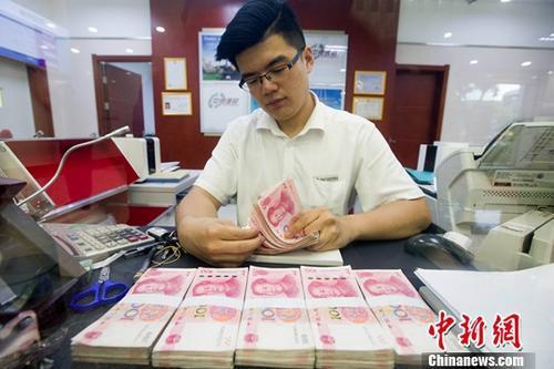 6月29日,山西太原一银行工作人员正在清点货币。中新社记者 张云 摄