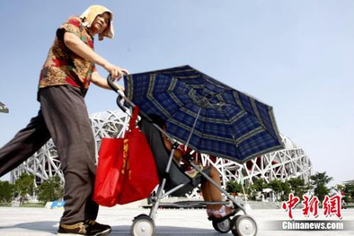 """资料图:立秋后的北京依然持续高温,人们用各种""""装备""""抵御""""秋老虎""""。中新社发 杜洋 摄"""