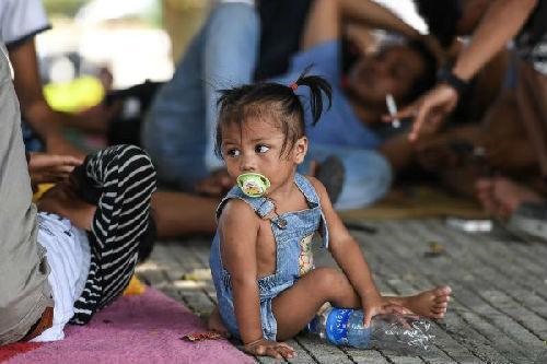 一小女孩在帕盧市災民安置點外(法新社)